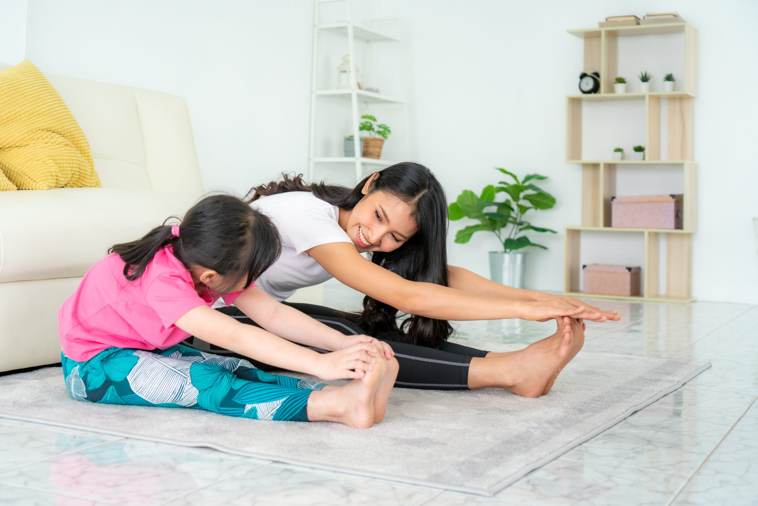 Asian,Mother,And,Daughter,Doing,Fitness,Exercises,In,Living,Room